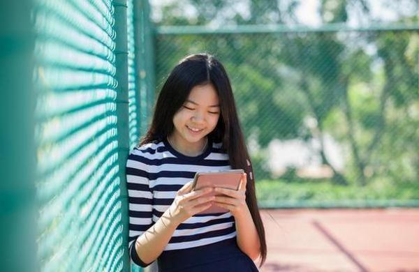 Young teen looking at her tablet while leaning against fence.